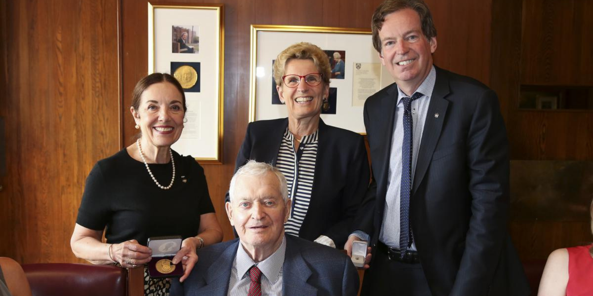 The Rt. Hon. John Turner receives a medal from Premier Kathleen Wynne and John Geiger, CEO of The Royal Canadian Geographical Society.