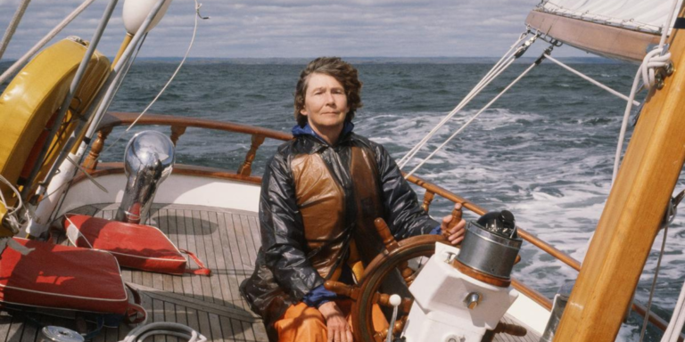 A woman drives a sailboat
