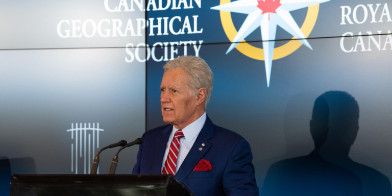 Alex Trebek stands at a podium behind the Royal Canadian Geographical Society logo