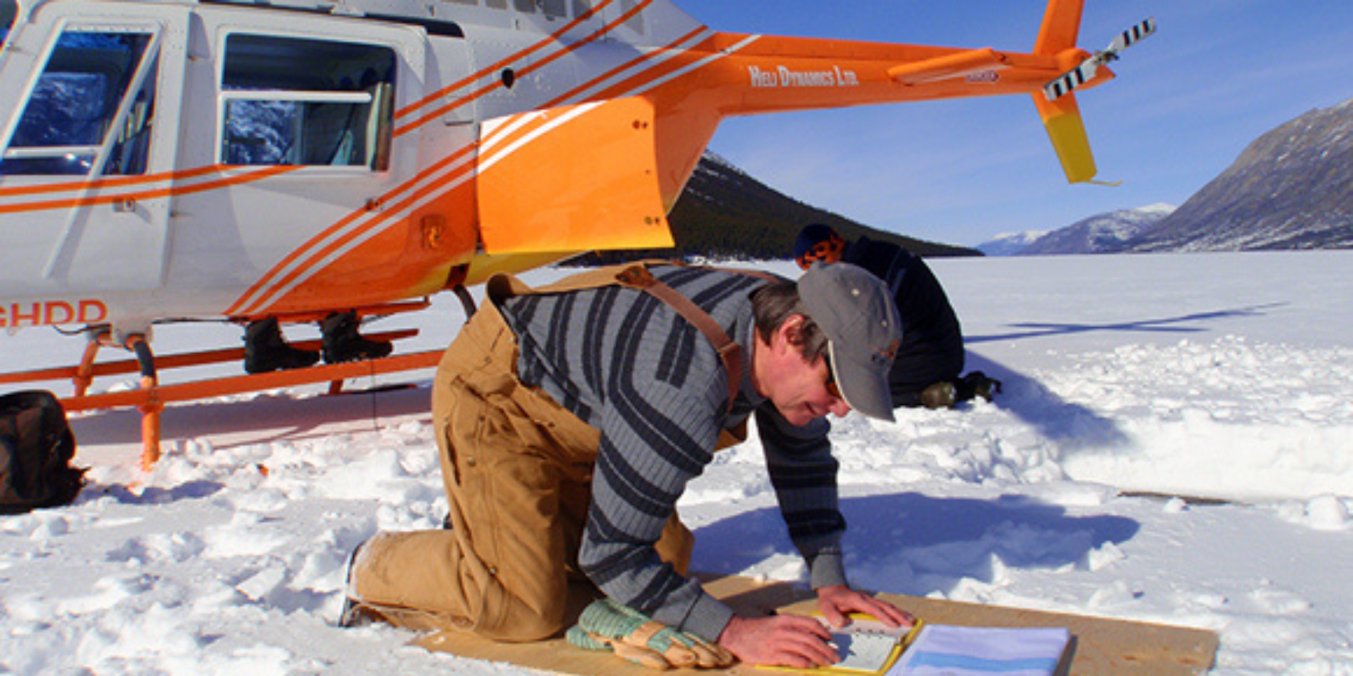 A man kneel to takes notes on the snowy ground in front of an orange and white helicopter