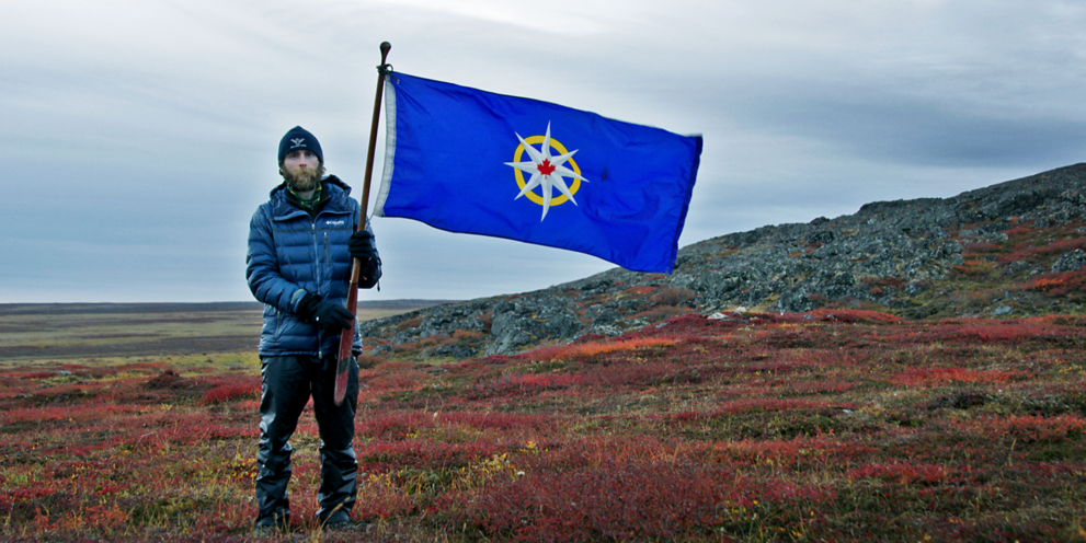 A man holds a flag in a arctic field