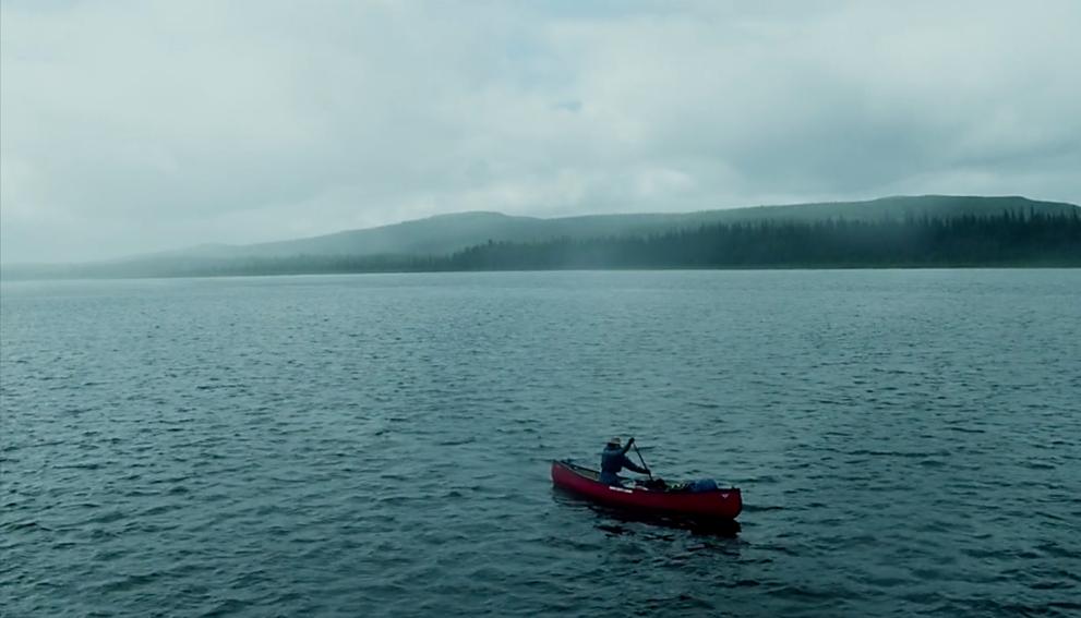 A man paddles a canoe on a lake
