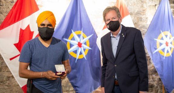 Gurdeep Pandher (left) receives the Louie Kamookak Medal from RCGS CEO John Geiger (right).