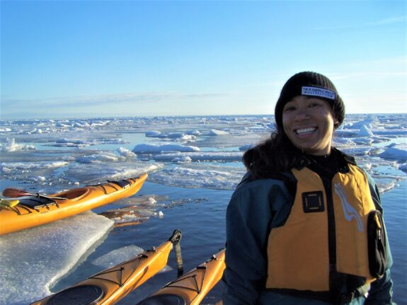 Emily Choy stands in front of an Arctic landscape in a yellow lifejacket alongside yellow kayaks