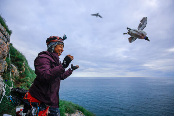 Emily Choy stands on a sea-side cliff as thick-billed murres fly overhead